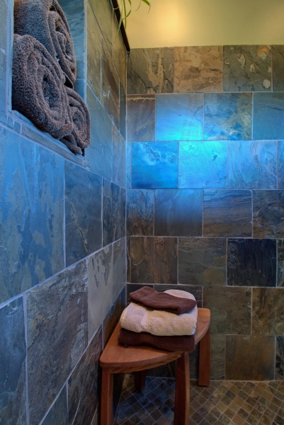 teak seat in walk-in shower, tiled with natural slate