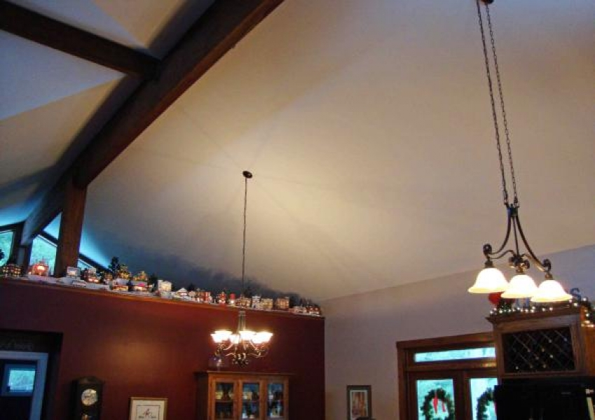 great room vaulted ceiling with exposed beams and partial wall