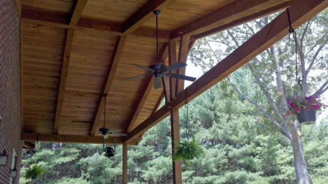 looking up under wood porch roof with exposed beams or other wood parts