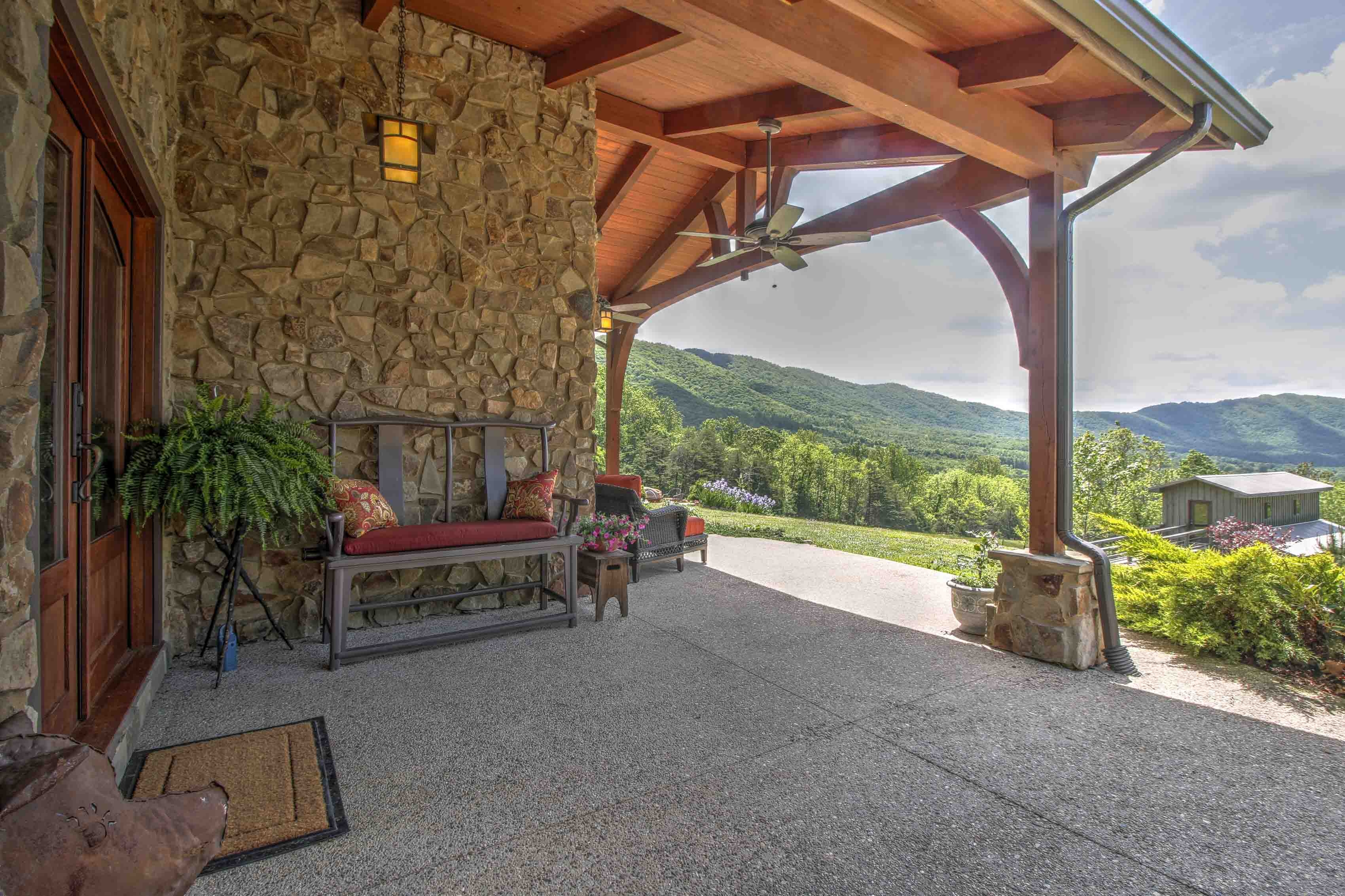 example of a timber frame porch featuring white oak with natural stone pedestals overlooking a mountain valley near Smith Mountain Lake, by Timber Ridge Craftsmen Inc. - Moneta, Virginia