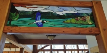 image of blue heron over Smith Mountain Lake featured as a transom at foyer of Heron Point; stained glass artwork by SER Art in Moneta; builder Timber Ridge Craftsmen Inc