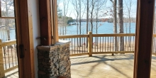 image of stone pedestal bisected by large glass window overlooking panoramic vista of Smith Mountain Lake, Heron Point; design details and builder Timber Ridge Craftsmen Inc.